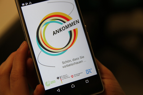 Die Begrüßungsseite der App Ankommen wird auf dem Display eines Smartphones gezeigt